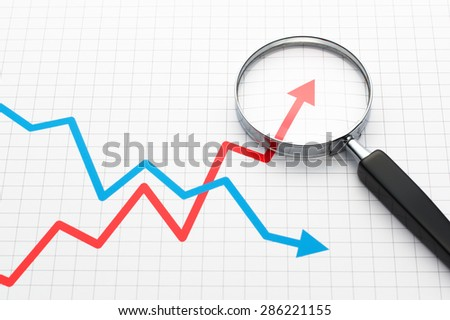 Looking growth field of line graph with magnifying glass. Line graph and magnifying glass.  - stock photo