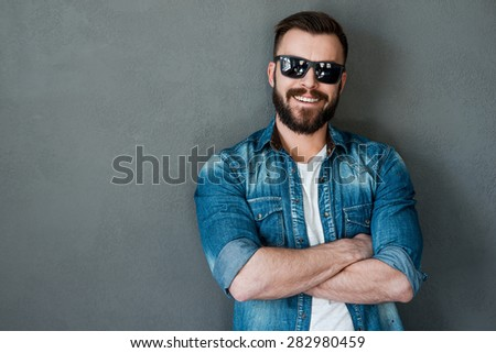Looking handsome and casual. Happy young man keeping arms crossed and smiling at camera while standing against grey background