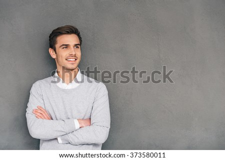 Looking in future with smile. Confident young man keeping arms crossed and looking away with smile while standing against grey background - stock photo