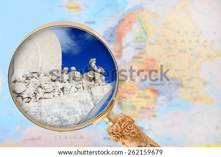 Looking in on the Explorers monument in  Portugal with a magnifying glass or loop with European map in the background - stock photo