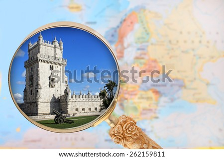 Looking in on Torre de Belem  a monument in  Portugal with a magnifying glass or loop with European map in the background - stock photo