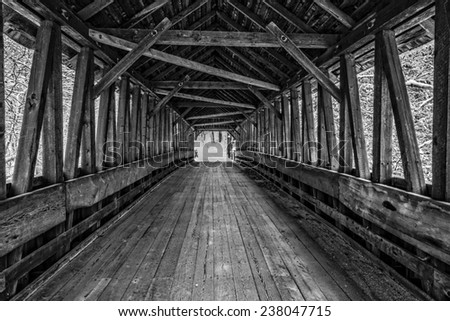 Looking inside an old wooden covered bridge in winter, Cornish, New Hampshire.  Black and white photograph. - stock photo