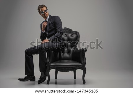 Looking just perfect. Full length of confident young businessmen in sunglasses sitting on the vintage chair while isolated on grey - stock photo