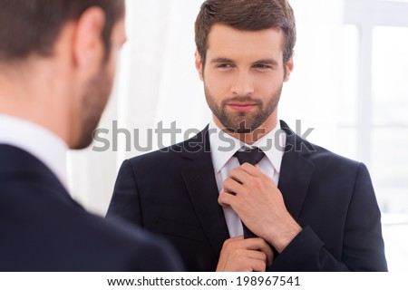 Looking just perfect. Handsome young man in formalwear adjusting his necktie and smiling while standing against mirror - stock photo