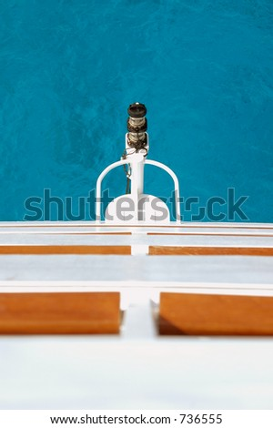 Looking off the rear of a cruise ship into aqua water - stock photo