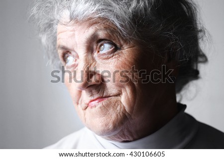 Looking old woman portrait on a gray background