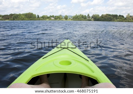 Looking out from a neon green kayak across calm lake waters at trees and houses across the lake during a summer holiday in Mont Laurier near Montreal, Quebec, Canada.