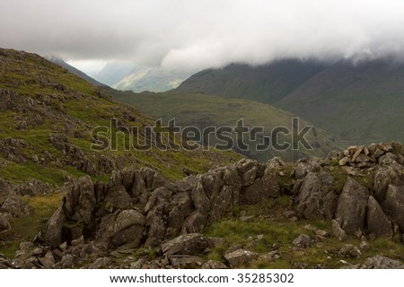 Looking out from a vantage point over a valley, this picture offers a view of rocks in the foreground, and a moody scene with low clouds in the background. - stock photo
