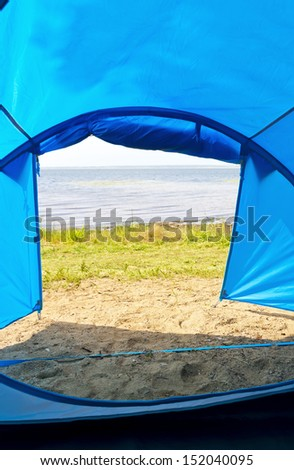 Looking out of open tent door upon calm lake - stock photo