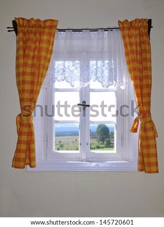 Looking out the old window with orange curtains - stock photo