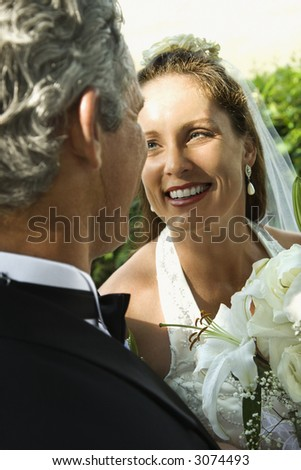 Looking over groom's shoulder at smiling bride. - stock photo