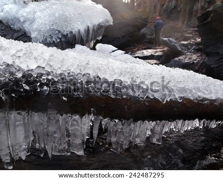 Looking past an extreme closeup of icicles on a log across a stream, a visitor in a red hat can be seen exploring a state park in the winter.  - stock photo