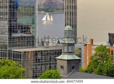 looking past the tall buildings of downtown Halifax towards the harbor, Tallship sailing by in between the buildings; Halifax Nova Scotia Canada - stock photo