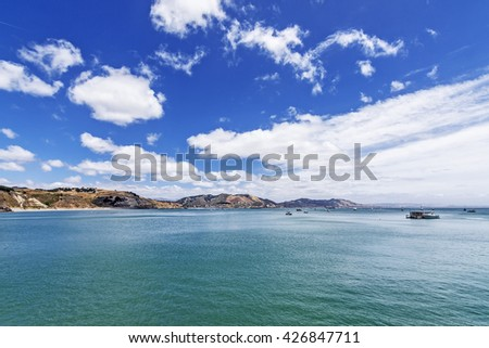 Looking south from the San Luis Port pier, you see beautiful blue sky and white clouds, aquamarine sea. In the background is the pier, at Avila Beach. Photographed on the California Central Coast.
