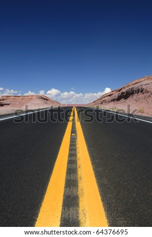 Looking straight down the highway in the desolate deserts of the southwestern United States. - stock photo