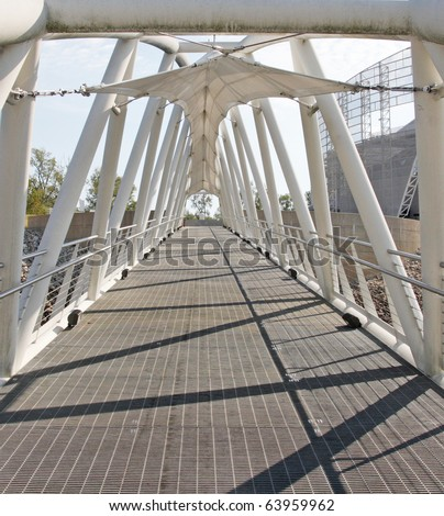 Looking straight through a white colored, covered, walkway bridge. - stock photo