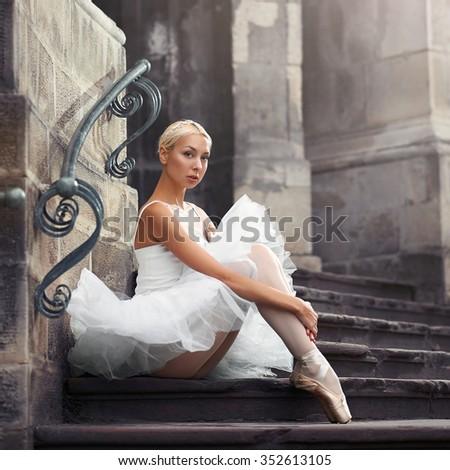 Looking thorough you. Portrait of a young ballerina sitting on an old stairway outdoors with her arms around her knees  - stock photo