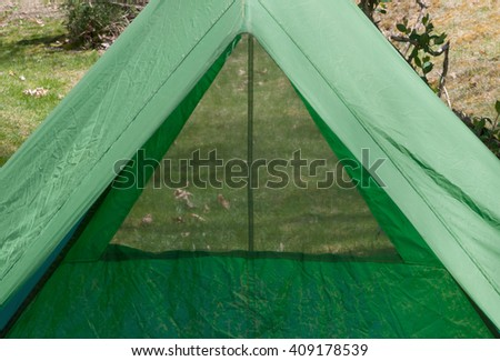 Looking  through a backpacking tent window through the length of the tent past the open door to ground outside. Tent is 40 years old, showing peeling waterproofing and general age. - stock photo