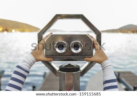 Looking through a coin operated binoculars, rear view - stock photo