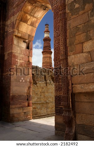 Looking through a gate at the red sandstone tower, Qutub Minar, in Delhi India. - stock photo
