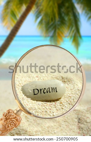 Looking through a magnifying glass on a stone saying Dream laying in the sand in a tropical paradise with palm tree and Caribbean ocean in the background - stock photo