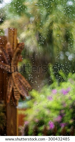 Looking through a rain soaked window out towards a colorful lush garden, focus is on rain drops on glass with garden out of focus. - stock photo
