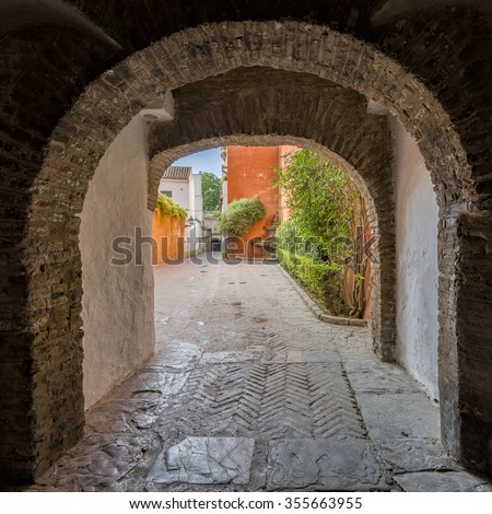 Looking through an archway, a view on an old but colorful street in the historical center of Seville, Spain - stock photo