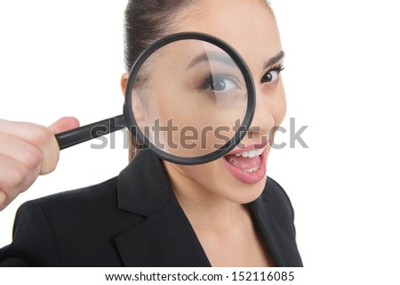 Looking through magnifying glass. Beautiful young woman looking through the magnifying glass and smiling while isolated on white - stock photo