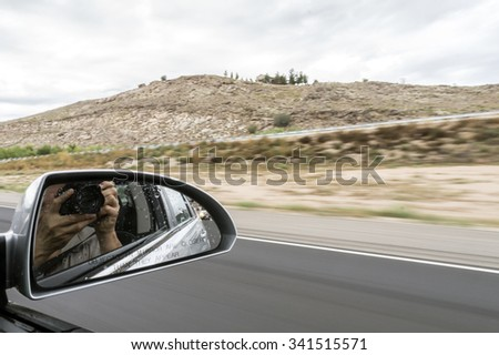 Looking through rear view mirror and shooting photograph in car - stock photo