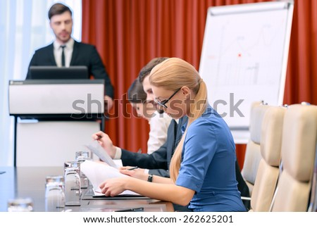 Looking through the documents. Closeup with selective focus on attractive blonde businesswoman in spectacles looking down to the papers while male business manager stands at the tribune on the - stock photo