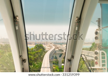 Looking through the front window of a commuter train to see a monorail track approaching a major urban center in the background. - stock photo