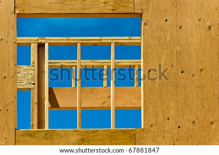 Looking through the opening for a window of an unfinished house.