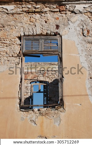 Looking through the windows of a derelict building at Emborio on the Greek island of Halki. - stock photo