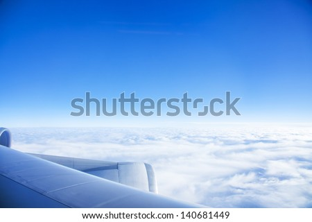 Looking through window aircraft during flight in wing with a blue sky - stock photo