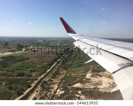 Looking through window aircraft during flight in wing with a city in Mandalay