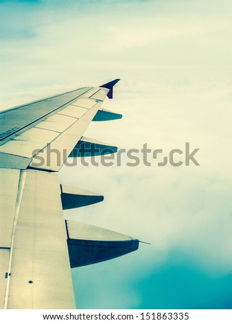 looking through window aircraft in wing aerial view of landscape and sky vintage - stock photo