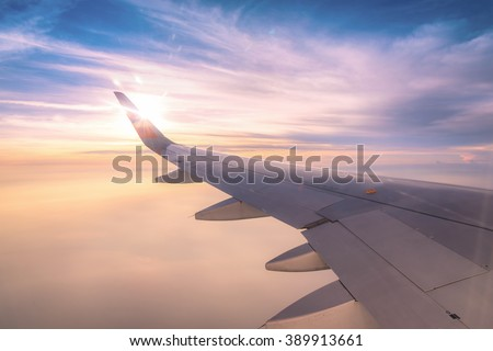 Looking through window aircraft wing during flight and look cloud in beautiful - stock photo