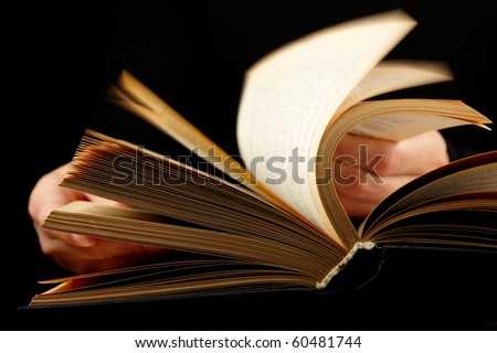 Looking thruogh book. With motion blur on black background - stock photo