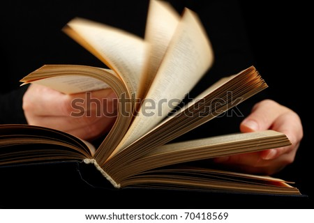 Looking thruogh book with motion blur on black  background - stock photo