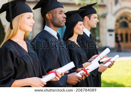 Looking to a bright future. Four college graduates holding their diplomas and looking away while standing in a row and in front of the university - stock photo