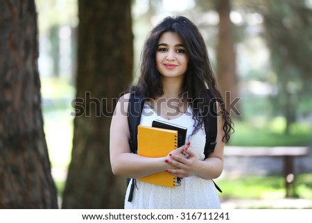 Looking to camera, student girl outdoors, with bag on backside, notebook on hand, exercise book, drawing block, beautiful student girl, young beautiful model, tajik girl - stock photo