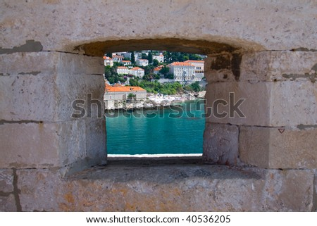 Looking to the sea through a window in the wall - stock photo
