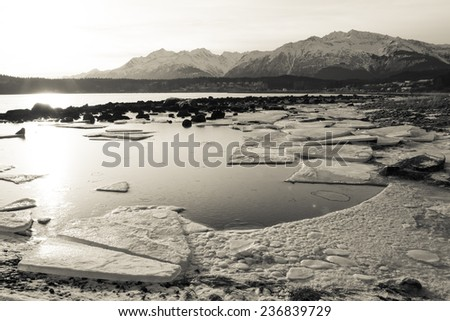 Looking towards Haines Alaska from Picture Point in winter with frozen chunks of ice on the beach. - stock photo