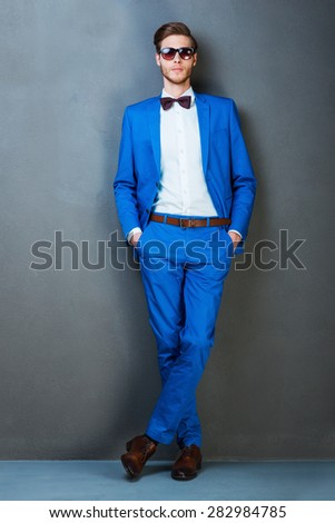 Looking trendy. Handsome young man in eyewear holding hands in pockets and looking at camera while standing against grey background - stock photo