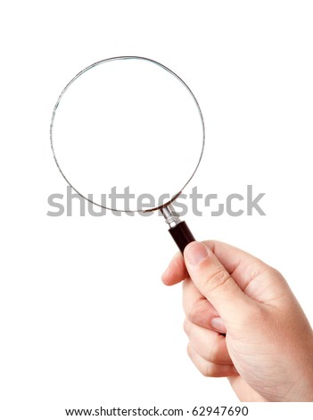 Looking trough magnifying glass in hand - stock photo