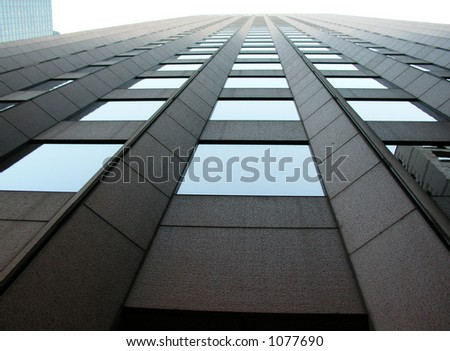 Looking up a tall mirrored building - stock photo