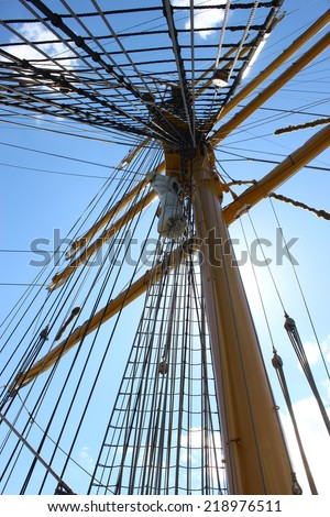 Looking up a tall ships sailing mast from below on the upper deck. - stock photo