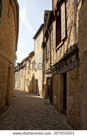 Looking up an old narrow French cobbled street with old buildings on either side