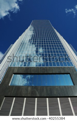 Looking up at a blue reflective glass office tower - stock photo