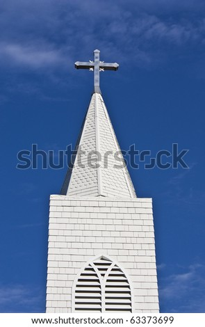 Looking up at a church steeple and cross - stock photo